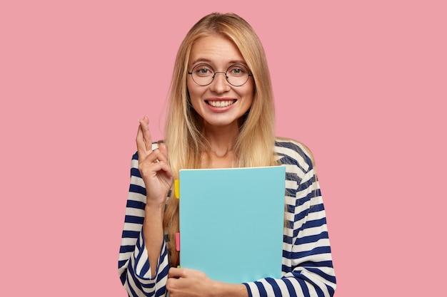 Обнадеживающая симпатичная студентка-блондинка держит пальцы скрещенными и верит в удачу