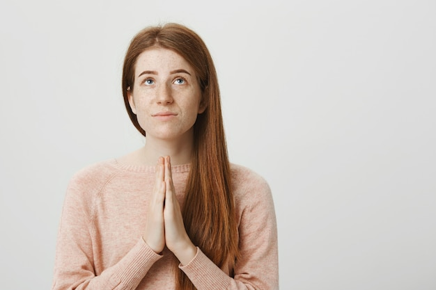 Hopeful redhead girl pleading god, hold hands in a prayer and looking up