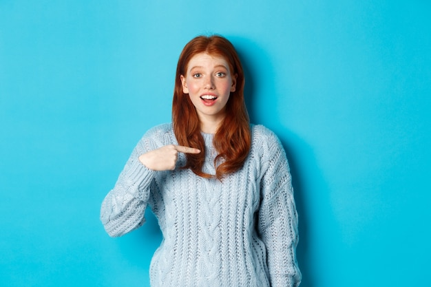 青い背景の上に立って、自分自身を指している希望に満ちた赤毛の女の子