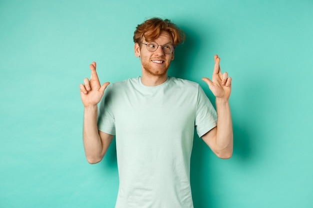 Hopeful redhead man in glasses making a wish, cross fingers and looking right at copy space, dreaming about something or making wish, standing over turquoise background.