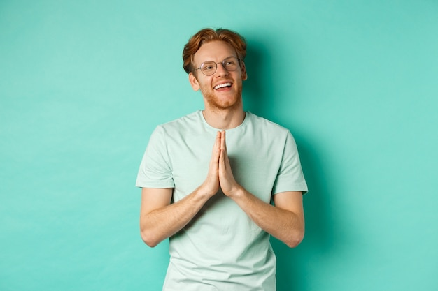 Hopeful redhead man with beard, wearing glasses and t-shirt, holding hands in namaste or plead gesture and looking right, smiling and thanking, standing over turquoise background.