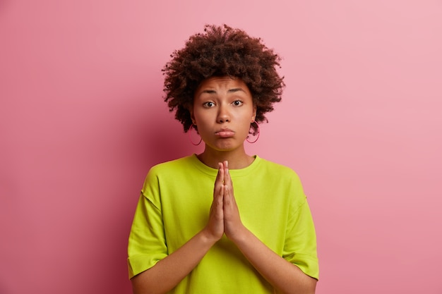 Hopeful sad woman presses palms together, pleads or asks apology, needs your help, wear green t shirt, poses against pink wall. please do me favor for last time. body language concept.