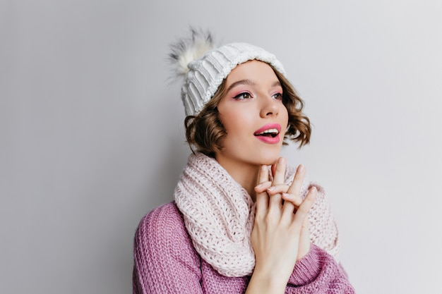 Hopeful short-haired curly girl in hat looking away. indoor close-up portrait of pretty dark-haired woman posing in knitted white scarf.