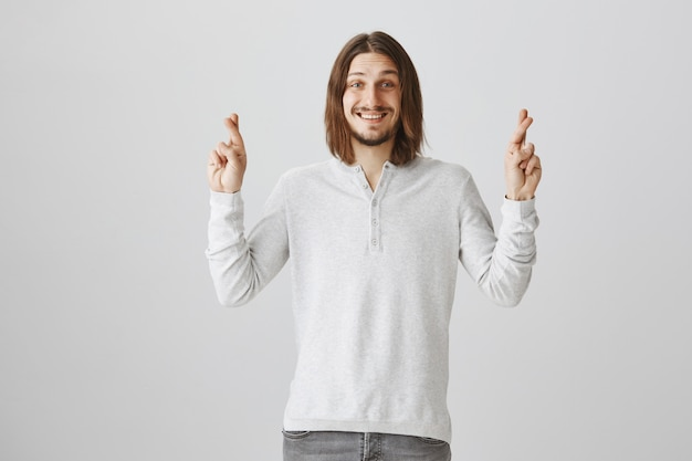 希望に満ちた笑顔と楽観的な男のクロスフィンガー幸運