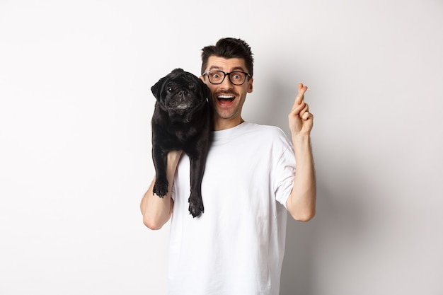 希望を持って笑顔の犬の飼い主が願い事をし、肩にかわいい黒いパグを持ち、幸運のために指を交差させ、白い背景。