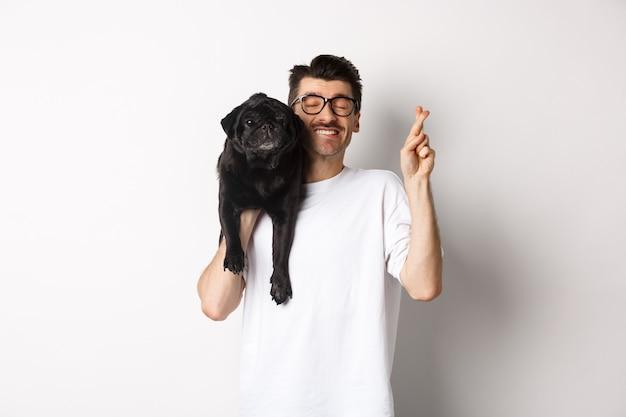 Надеясь улыбающийся владелец собаки загадывает желание, держа милого черного мопса на плече и скрестив пальцы на удачу, белый.