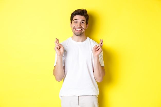 黄色の背景の上に立って、指を交差させ、願い事や祈りをして、希望に満ちた笑顔の男