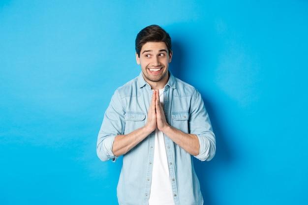 左を見て、祈って手をつないで、何かを物乞いしたり、懇願したり、青い壁に立って、希望に満ちた笑顔の男