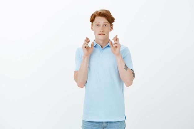 希望に満ちた笑顔の赤毛の男は良いニュースを期待し、幸運のために指を交差させます