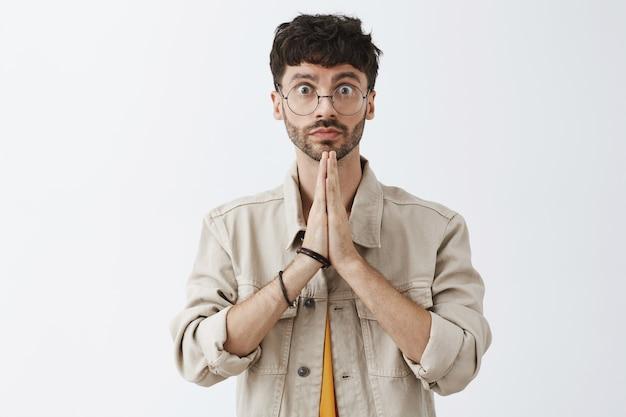 Hopeful stylish bearded guy posing against the white wall