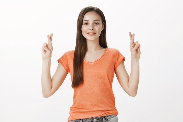 Bella ragazza speranzosa e desiderosa che prega, incrocia le dita, buona fortuna, esprime il desiderio