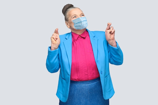 外科医療マスクの女性が指を交差させて希望を持って希望を持っています。集めたパンの髪で立っている水色のスーツとピンクのシャツを着た祖母。灰色の背景で分離された屋内スタジオショット