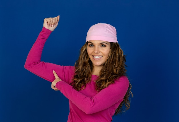白い壁に分離されたピンクのスカーフを身に着けている希望に満ちた女性
