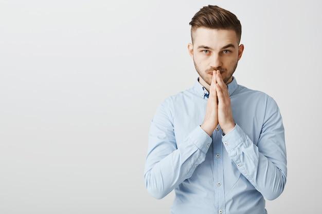 Обнадеживающий обеспокоенный бизнесмен молится, взявшись за руки в мольбе, ожидая результатов