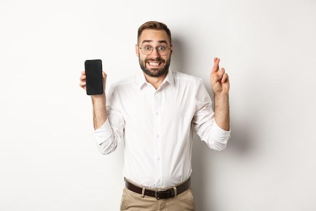 Promettente giovane uomo d'affari che mostra lo schermo del cellulare, tenendo le dita incrociate, in attesa di risultati online, in piedi