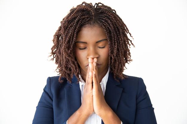 Hopeful young businesswoman praying