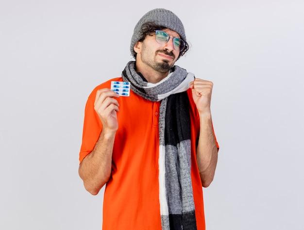 Speranzoso giovane indoeuropeo uomo malato con gli occhiali inverno cappello e sciarpa che tiene il pacchetto di capsule mediche facendo essere forte gesto con gli occhi chiusi isolato su sfondo bianco con spazio di copia