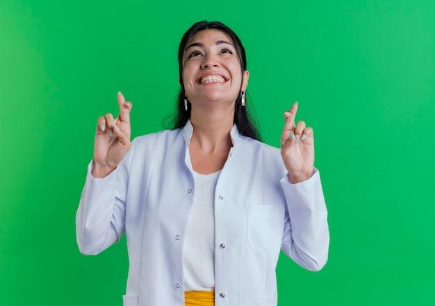 コピースペースのある緑の壁に隔離された幸運を願って交差する指を見上げる医療ローブを身に着けている希望に満ちた若い女性医師