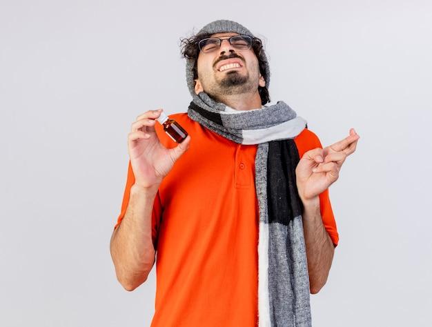 Speranzoso giovane uomo malato con gli occhiali inverno cappello e sciarpa che tiene medicamento in vetro incrociando le dita che desiderano buona fortuna con gli occhi chiusi isolati sul muro bianco