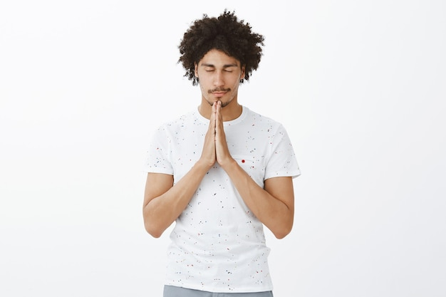 Hopeful young man praying, close eyes and pleading with hands clasped together
