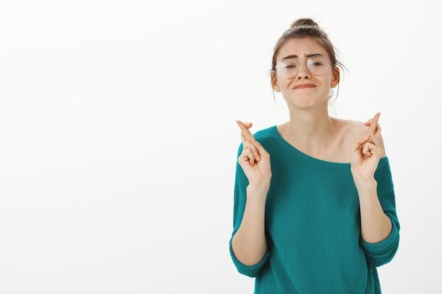 La giovane donna promettente incrocia le dita in bocca al lupo, esprimendo desideri o pregando