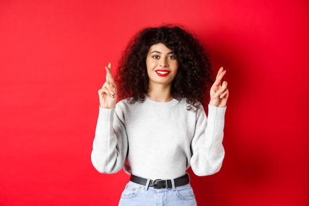 Speranzosa giovane donna con labbra rosse e capelli ricci, incrociare le dita per buona fortuna e esprimere desideri, pregando per il sogno che si avvera, sorridendo eccitato, sfondo rosso