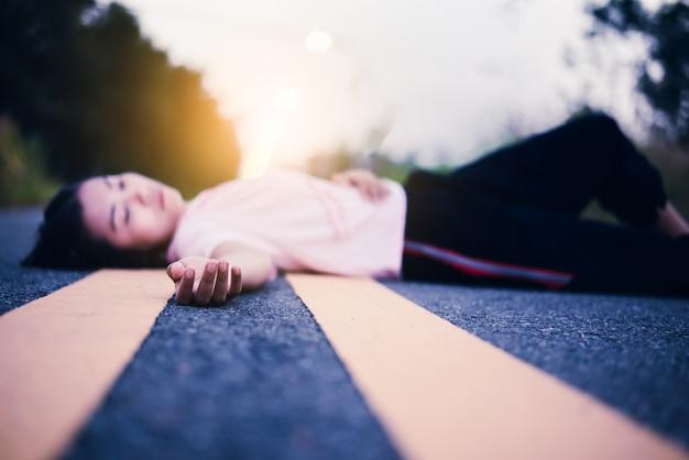 Hopeless girl lying down on street at sunset