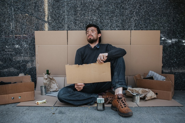 Hopeless and homeless person is sitting on cardboard on the ground and holding a piece of cardboard