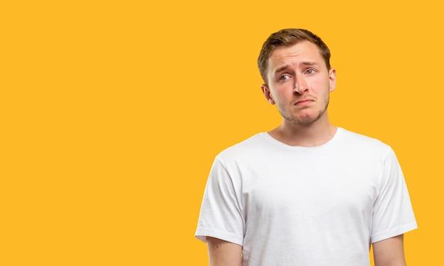Безнадежный мужской портрет. утрата отчаяния. разочарованный парень в белой футболке изолированной на оранжевом фоне.