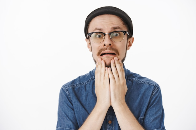 검은 비니에 수염을 가진 절망적 인 문제가있는 잘 생긴 남자와 턱에 손바닥을 들고 안경을 찌푸리고 회색 벽을 쳐다보고 끔찍한 상황에 처한 동안 찡그린 얼굴