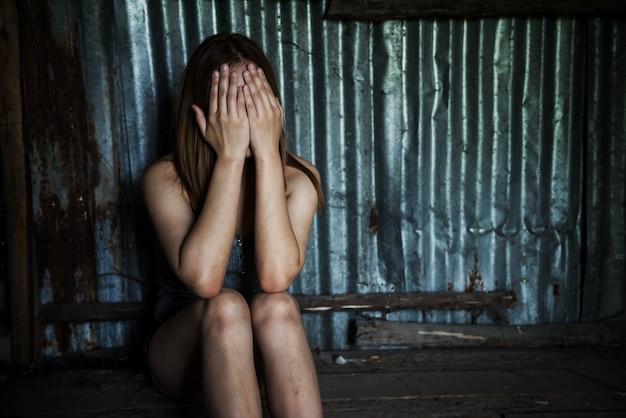절망적 인 실업자 여성은 폐허가 된 오두막이나 집에 앉아 울면서 손으로 얼굴을 가리고 있습니다.