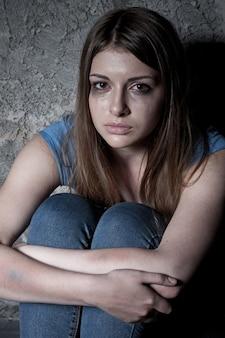 희망이 없는 여자. 어두운 벽에 앉아 울고 카메라를 바라보는 젊은 여성의 상위 뷰