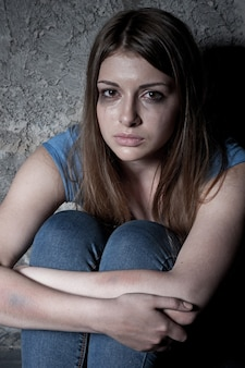 Hopeless woman. top view of young woman crying and looking at camera while sitting against dark wall