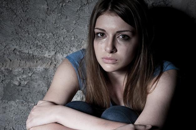 가망 없음. 어두운 벽에 앉아 울고 카메라를 바라보는 젊은 여성의 상위 뷰