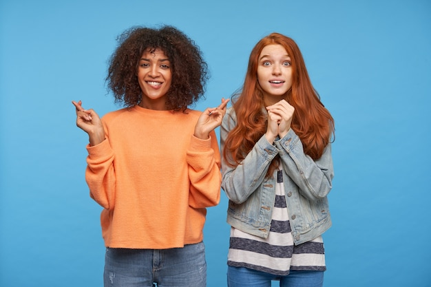 Hoping attractive young women looking worringly  and keeping their hands raised, isolated over blue wall in casual wear