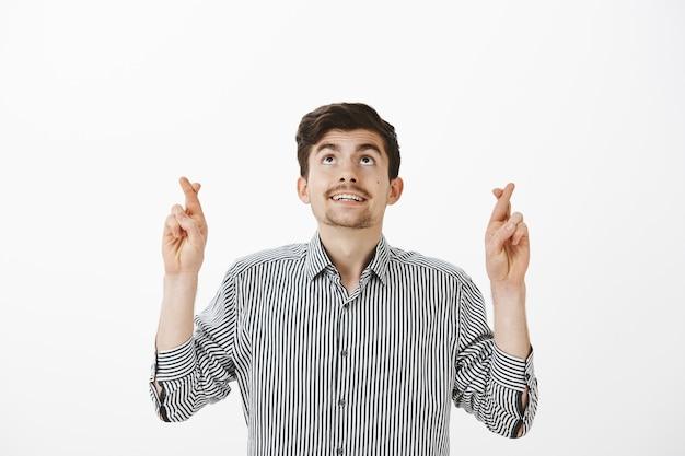 ストライプのシャツを着たうれしそうな魅力的なひげを生やした男が指を交差させながら見上げて、成功するか祈りながら祈り、灰色の壁を越えて最高の結果が得られると確信して祈る