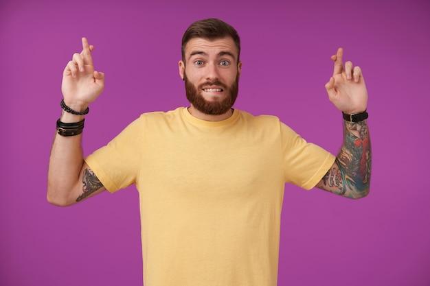 소원을 만들고 손가락을 건너는 문신을 가진 예쁜 수염 난 갈색 머리 남성을 기대하고, 노란색 티셔츠에 보라색에 포즈를 취하는 언더 립을 물고