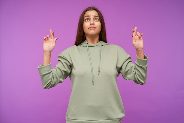 Hoping young green-eyed brunette woman with natural makeup crossing her fingers for good luck while looking upwards, standing against purple wall
