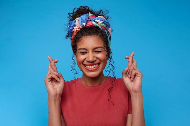 若い素敵なブルネットの巻き毛の女性が目を閉じて幸せに笑って、青い壁に隔離された願いをしながら幸運のために手を交差させることを願っています