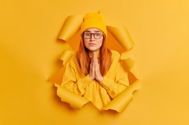 絶望的な悲しい女性は、手のひらを一緒に保ち、謝罪を求める表情が黄色い帽子とセーターを着ていることを嘆願しています。
