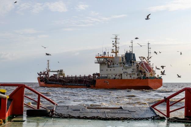 Земснаряд в море. судно занято дноуглубительными работами. строительство морские морские работы. строительство плотины, кран, баржа, земснаряд.
