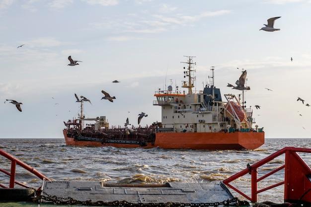 Hopper dredger at sea. vessel engaged in dredging. construction marine offshore works. dam building, crane, barge, dredger.