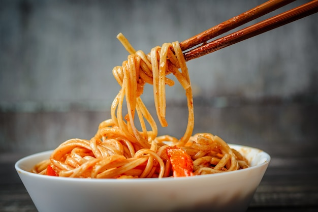 Hopsticks take noodles udon in sweet and sour sauce from plate. traditional asian cuisine
