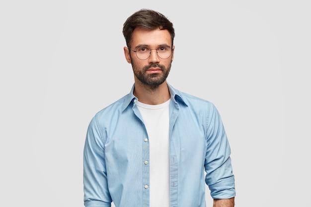 Горизонтальный снимок красивого мужчины-фрилансера с густой щетиной, одетого в модную рубашку