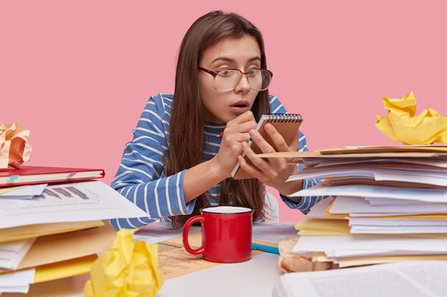 Горизонтальный вид: испуганная школьница смотрит на спиральный блокнот, записывает дату окончания написания курсовой работы, понимает, что времени у нее мало