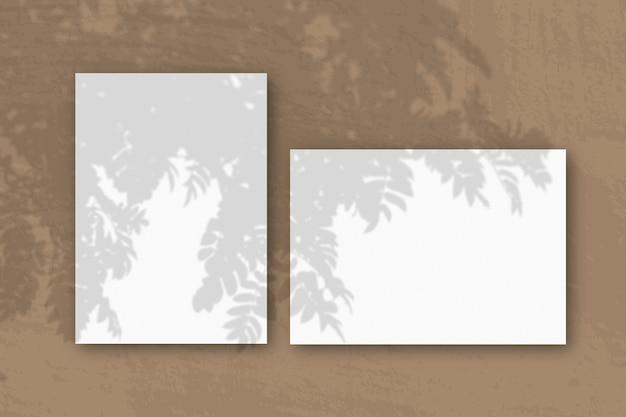 Горизонтальные и вертикальные листы белой текстурированной бумаги на коричневой стене