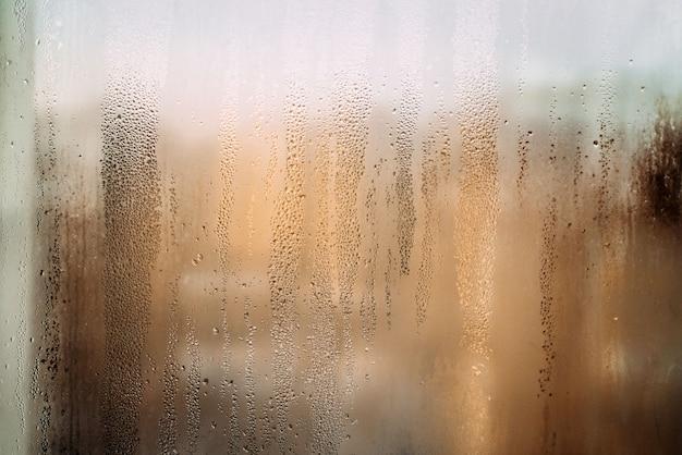 雨の後の太陽と滴の濡れた窓の水平背景テクスチャ暖かい写真高品質