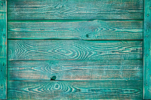 Horizontal background of wooden boards painted with green paint and fastened with a thin plank on the sides.