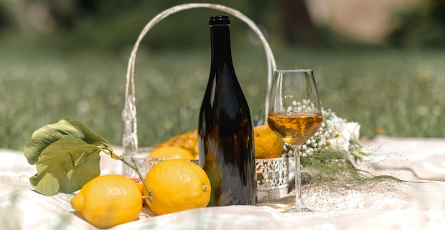 Horizontal banner or header close-up of wineglass full of white wine, an empty bottle and wine flavors around. picnic basket full of variety of tropical fruits on a picnic blanket.