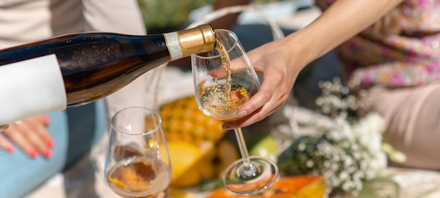 Horizontal banner or header of unrecognizable woman pouring white wine into a glass. picnic with tropical fruit on background.